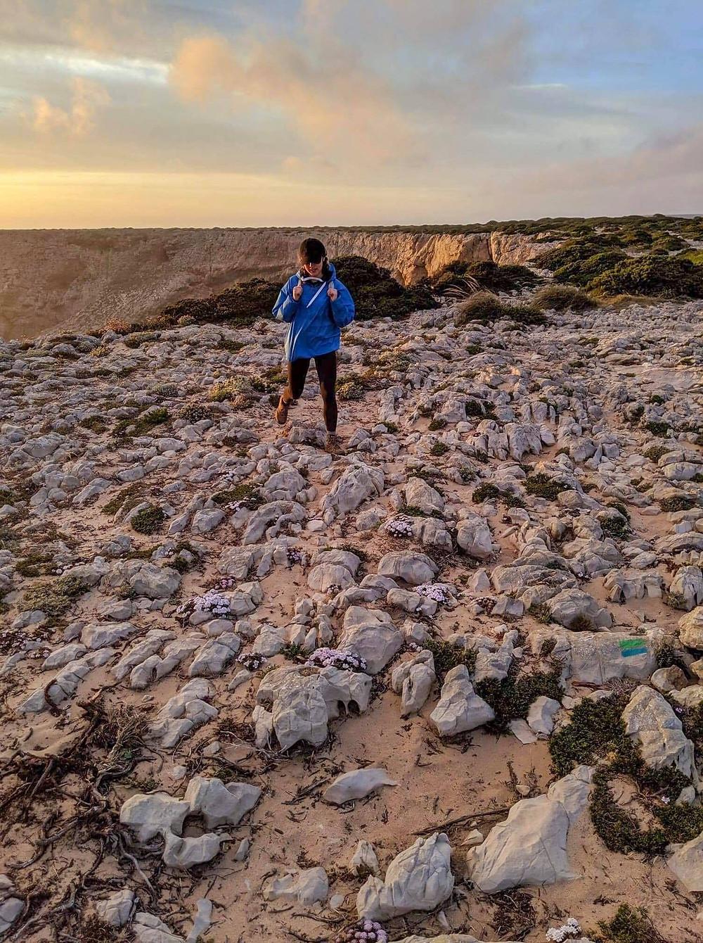 Girl travel blogger hiking in Portugal Algarve during sunset.