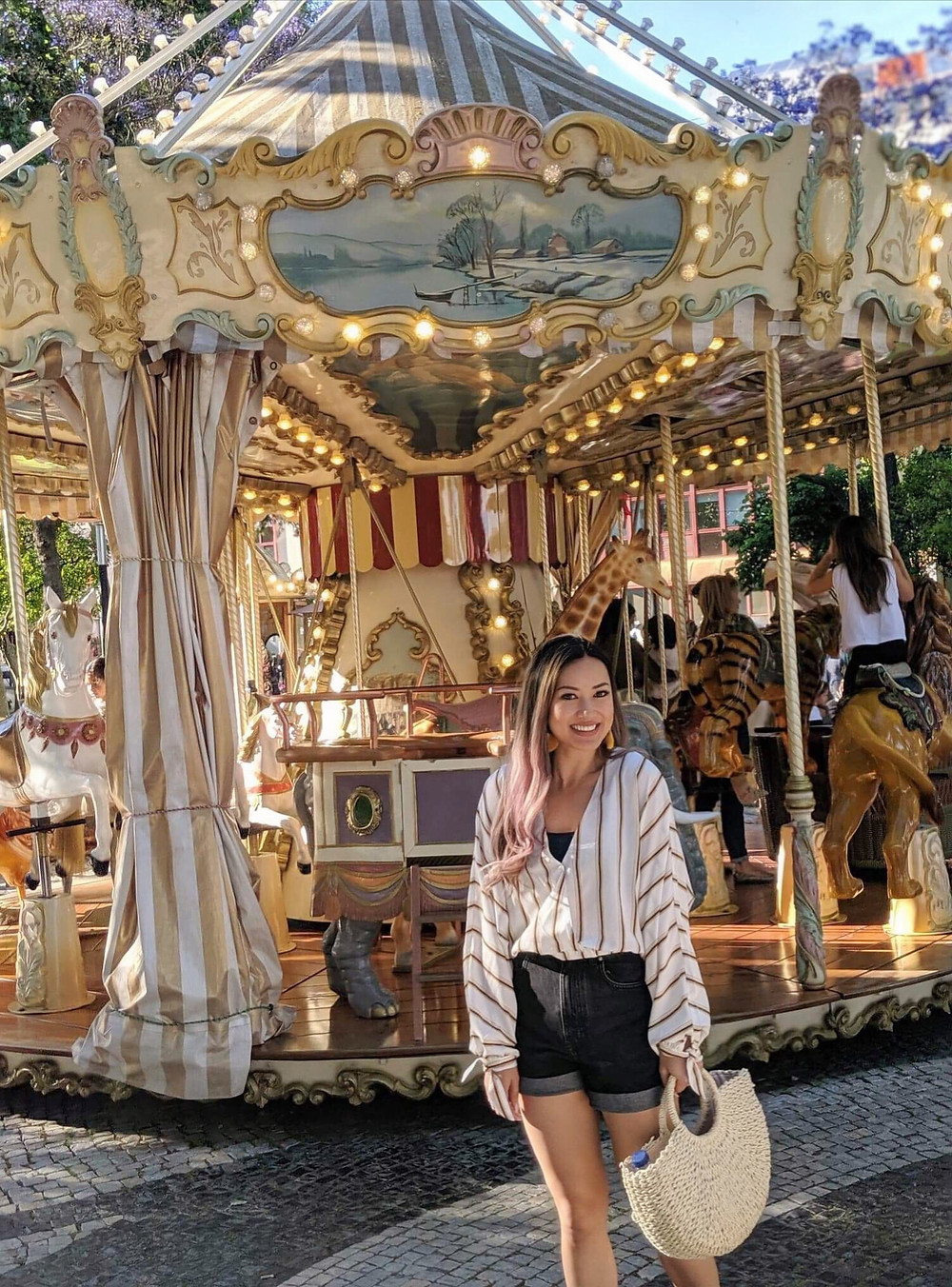 photograph of girl fashion travel blogger in fun boating outfit exploring downtown city center of Old Town Cascais Portugal, admiring the fun carousel downtown with lights.