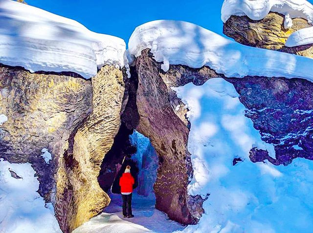 Girl travel fashion blogger hiking on frozen river in Lake Louise Yoho National Park by Emerald Lake British Columbia in winter.