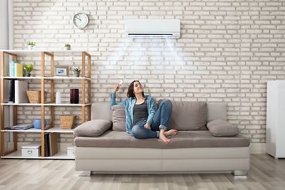 Happy Young Woman Holding Remote Control Relaxing Under The Air Conditioner.jpg