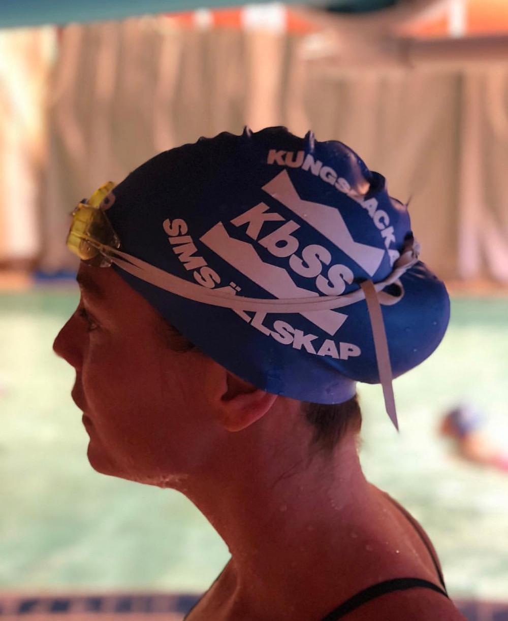 Emma Igelström i profil med badmössa i simhallen