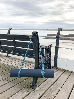 macrame yoga mat strap on bench in front of sea