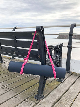 yoga macrame mat strap in hot pink on bench in front of sea