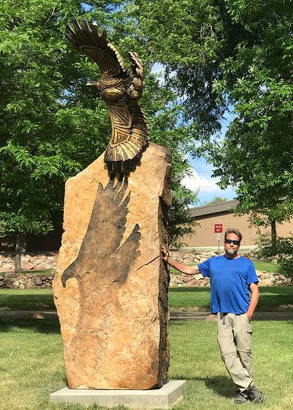 Public sculpture of eagle. Sculptor Adam standing beside it.