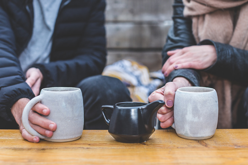 two people, man and woman drinking hot cups of tea