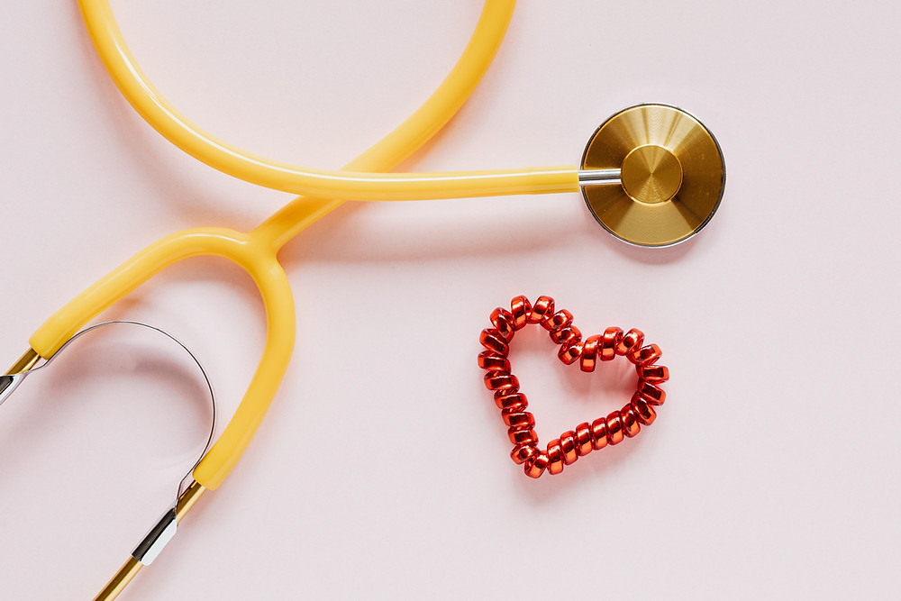 Yellow stethoscope and red heart beside it for benefits of love on your health