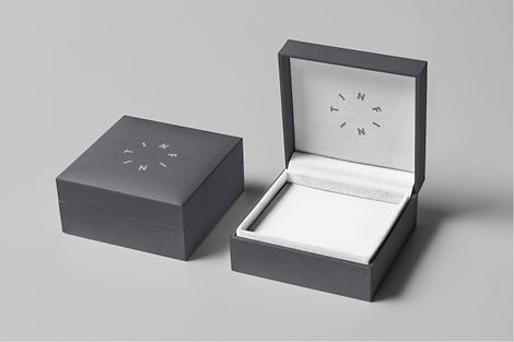 Opened up ring box with grey exterior and a circular Infiniti logo design debossed on white interior.