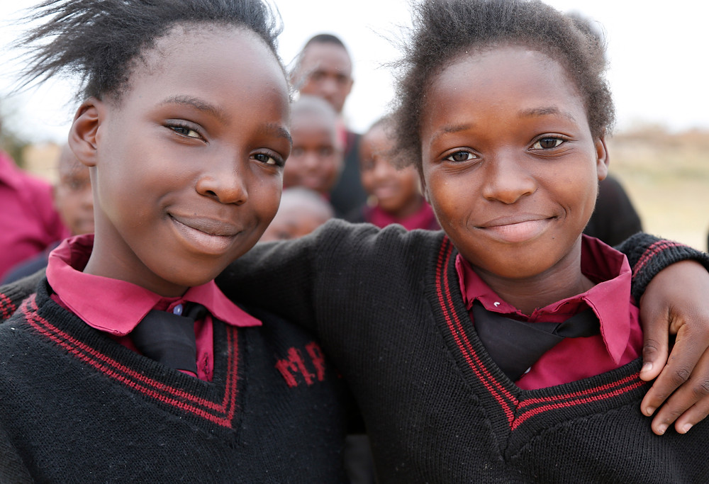 Two School-Aged girls smiling with their arms around each other.