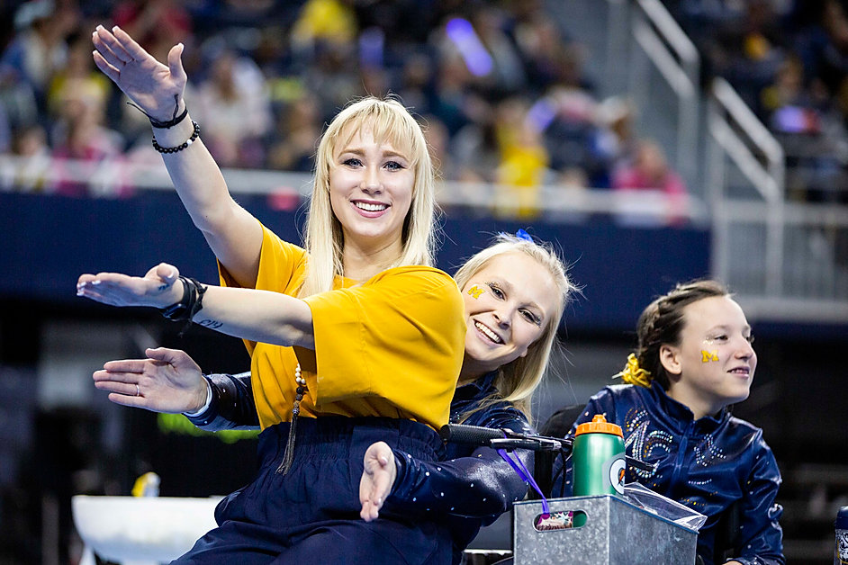 Student assistant coach Polina Shchennikova and junior Maggie O'Hara smile during a break in between the beam routines during a meet against Oklahoma at Crisler Center on March 9th, 2019.