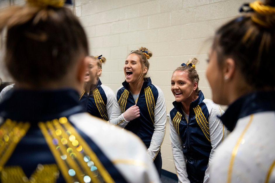 Sophomore Anna Dayton and junior Lexi Funk cheer along with the team before introductions in a meet against Iowa at Crisler Center on February 10th, 2019.