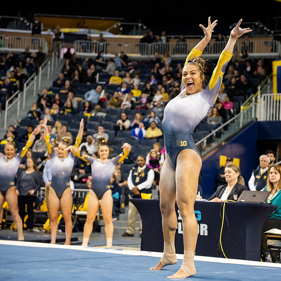 Senior Olivia Karas celebrates landing a pass during her floor routine in a meet against Iowa at Crisler Center on February 10th, 2019.
