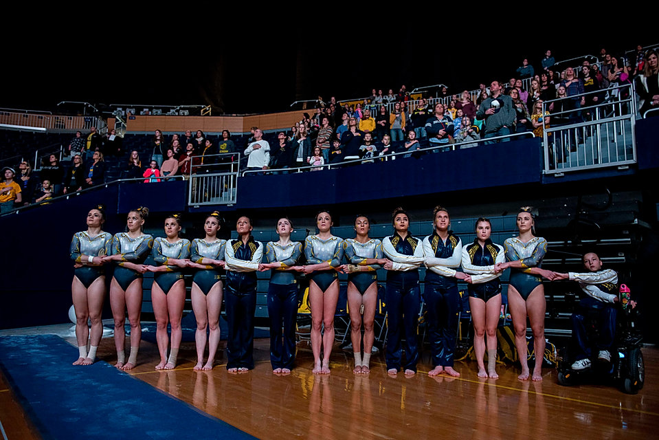 The team holds hands during the national anthem before a meet against Iowa on February 10th, 2019.