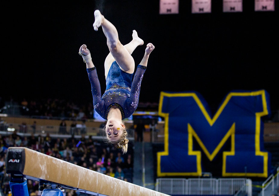 Sophomore Lauren Farley flips during her beam routine during a meet against Oklahoma at Crisler Center on March 9th, 2019.