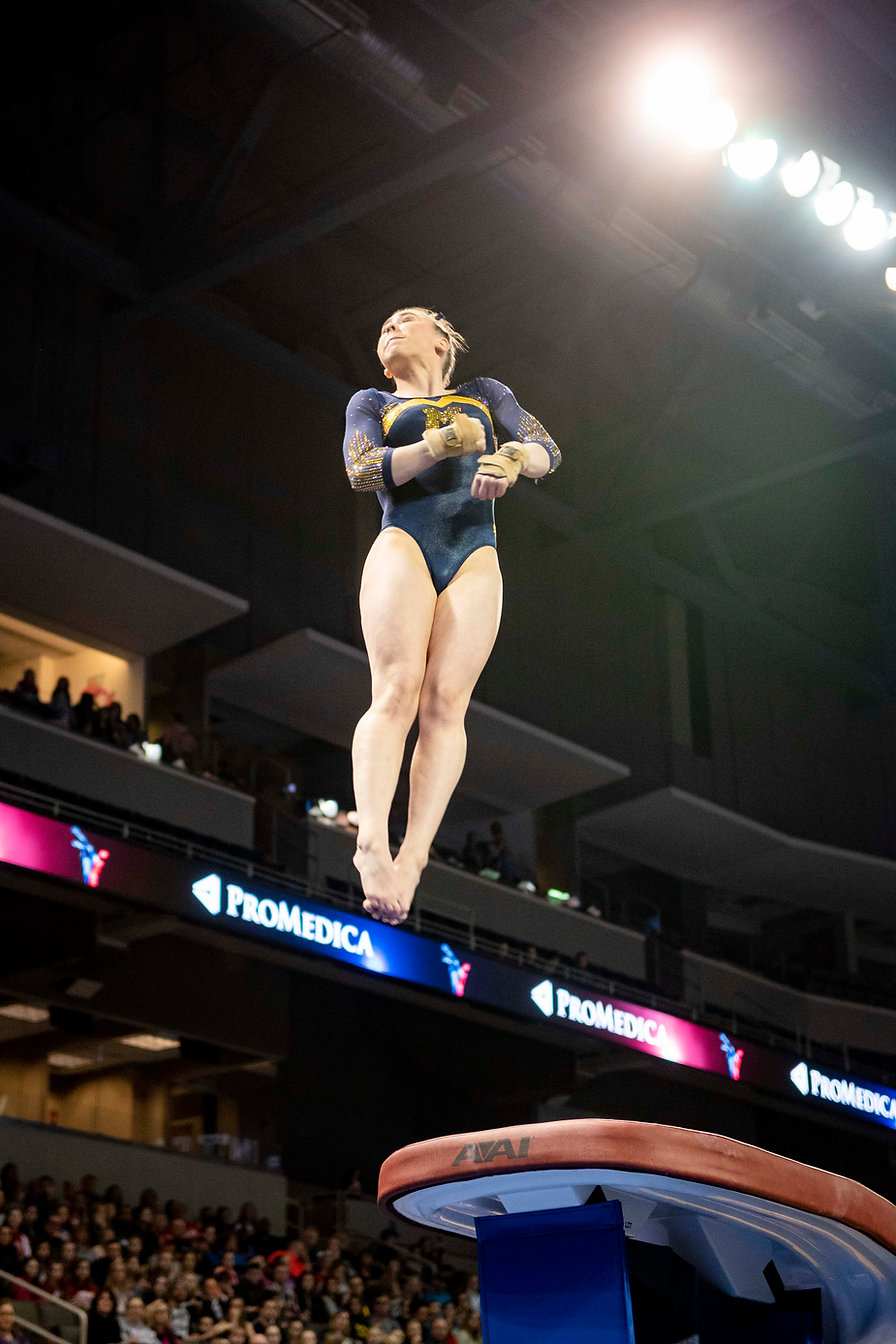 Freshman Natalie Wojcik twists herself during her vault routine during the Elevate the Stage meet. This was the vault that scored her a 10 and probably influenced her winning the Big Ten Freshman of the Year.