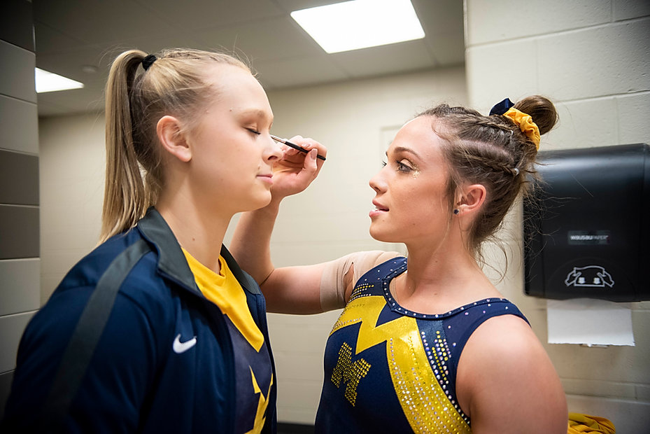 Senior Emma McLean puts sparkles on junior Maggie O'Hara before the Elevate the Stage meet in the locker room. The girls always put sparkles on, no matter what. During this competition, they actually gave me some sparkles as well.