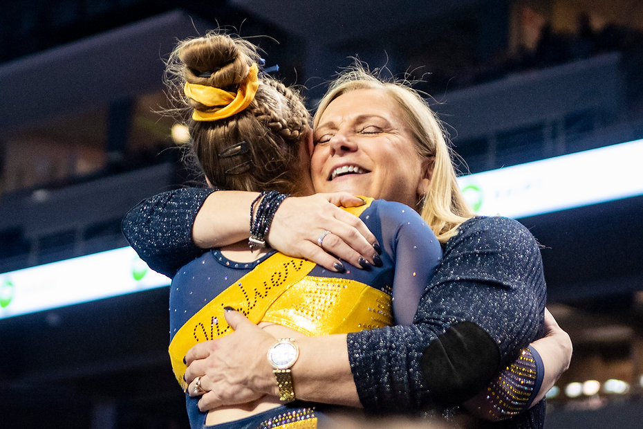 Coach Bev Plocki hugs one of her gymnasts after her beam routine during the Elevate the Stage meet.