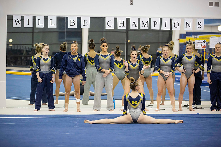 Teammates Lauren Farley, Olivia Karas, Sam Javanbakht, Maddy Osman, Abby Heiskell, Anne Maxim, and Maggie O'Hara watch and cheer on freshman Natalie Wojcik as she does the splits during her floor routine at the Donald R. Shepherd Women's Gymnastic Center.