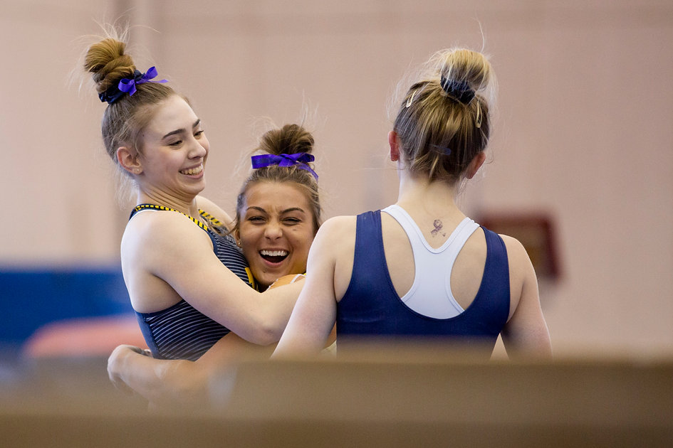 Senior Olivia Karas and sophomore Lauren Farley congratulate freshman Natalie Wojcik on landing her dismount from beam during practice.