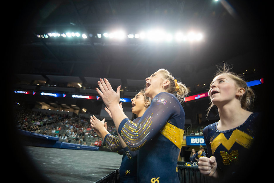 Sophomores Sam Javanbakht, Anne Maxim, and Lauren Farley cheer on junior Maddy Osman on beam during the Elevate the Stage meet. Essentially everyone who is not performing is cheering on the gymnast who is.