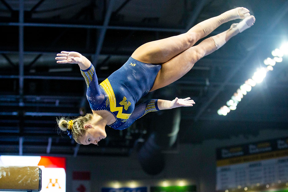 Junior Lexi Funk dismounts from the beam during the Elevate the Stage meet against Illinois, Rutgers, Ohio State, and Minnesota at the Huntington Center in Toledo, OH.