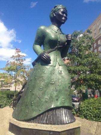 Ecco una delle statue più significative erette per l'eroina nel quartiere di Harlem, a New York. La statua rappresenta la Tubman nell'atto di portare in salvo attraverso le ferrovie sotterranee alcuni suoi compatrioti schiavi, che vengono disegnati sulla gonna di lei quasi a rappresentare che la loro vita era nelle sue mani. Le faccine sembrano spuntare dalla gonna ma non hanno lineamenti precisi,a indicare che non si tratta di personaggi definiti ma simbolici.