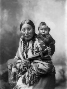 Ecco una donna Dakota con bambino.1899. L'usanza di legarsi il bambino sulla schiena è tipica di molti popoli primitivi e consentiva loro di lavorare, raccogliere e anche coltivare non perdendo di vista il figlio neonato.