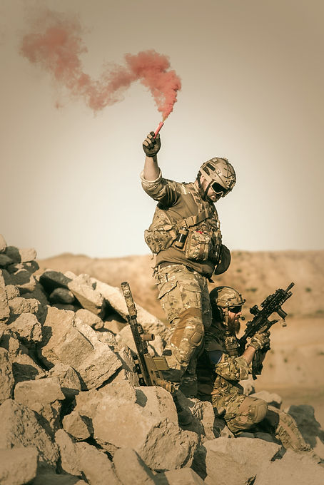 Man holding red smoking flare for tactical extraction.