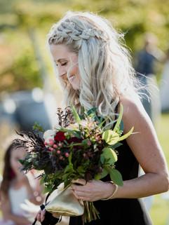 Bridesmaid walks down aisle with flowe
