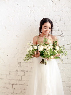 bride with flowers against a brick wall