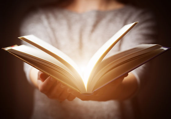 Light coming from book in woman's hands in gesture of giving, offering. Concept of wisdom,