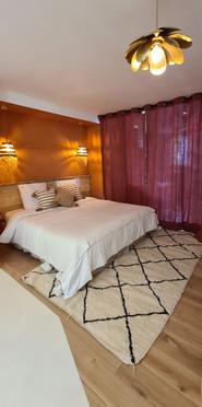 un lit grande largeur sur tapis confortable en laine