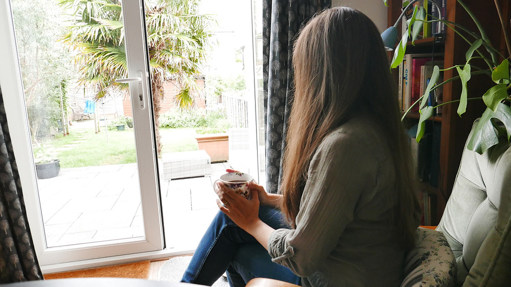 Women sits with a cup of tea and looks out of the window