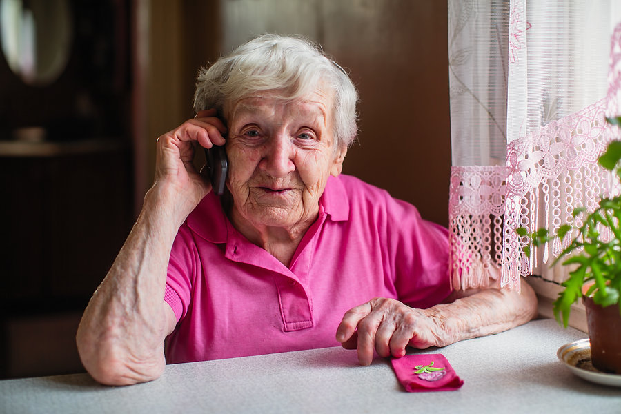 Elderly woman sitting at home and on the phone