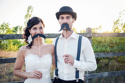 A bride and groom with their arms around each other, holding fake mostache's to their lips.