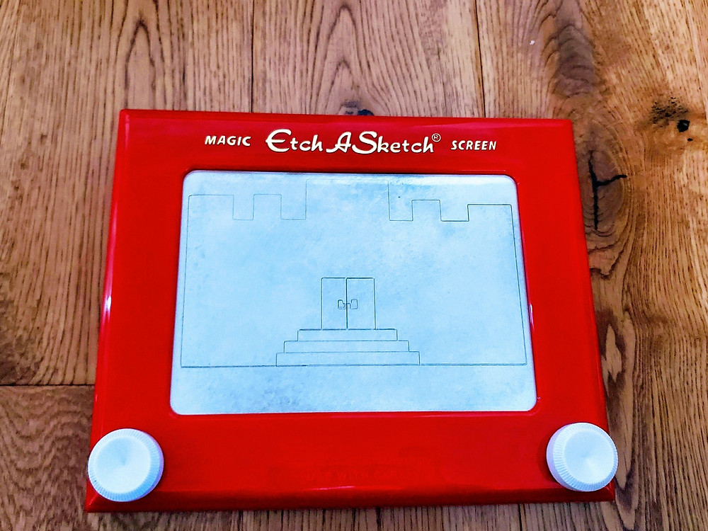 Picture of an Etch A Sketch on the floor.