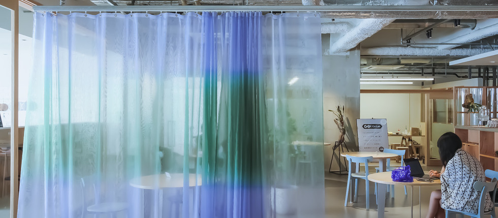 無骨な空間を彩る鮮やかなカーテンでゆるく仕切られたワークスペース