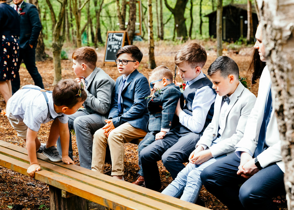 Children sat on bench in suits waiting for bride to arrive at Cheshire Woodlands Wedding