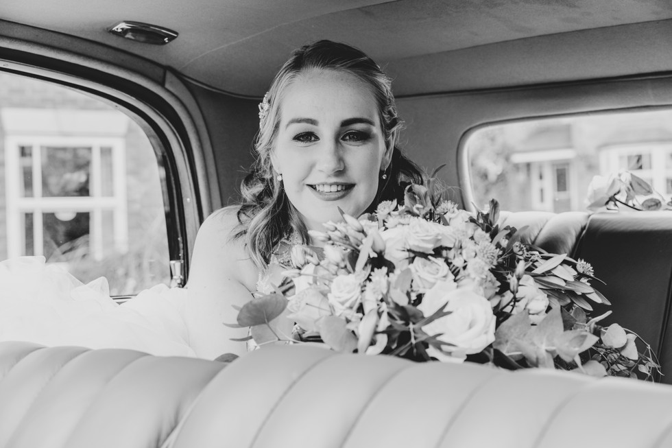 Bride on way to Wedding at Statham Lodge in back of Vintage Car