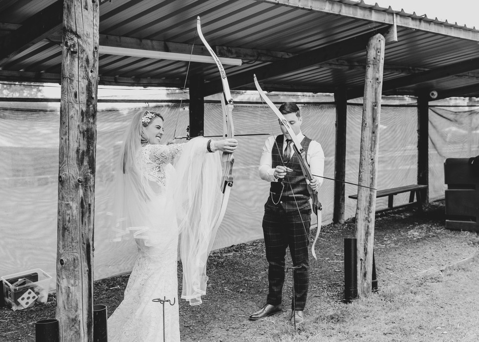 Bride and Groom take part in Archery at Cheshire Woodland Wedding