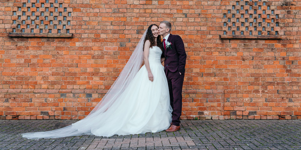 Statement photos of Bride and Groom against brick wall at stratford park hotel