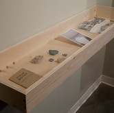 """Vitrine from the series 'i am a rock. i am an island.' 2012, 48""""x12"""" Items in vitrine include: color photograph, Icelandic guide book from WWII, minerals specimens, crying journal, and vials of tears."""
