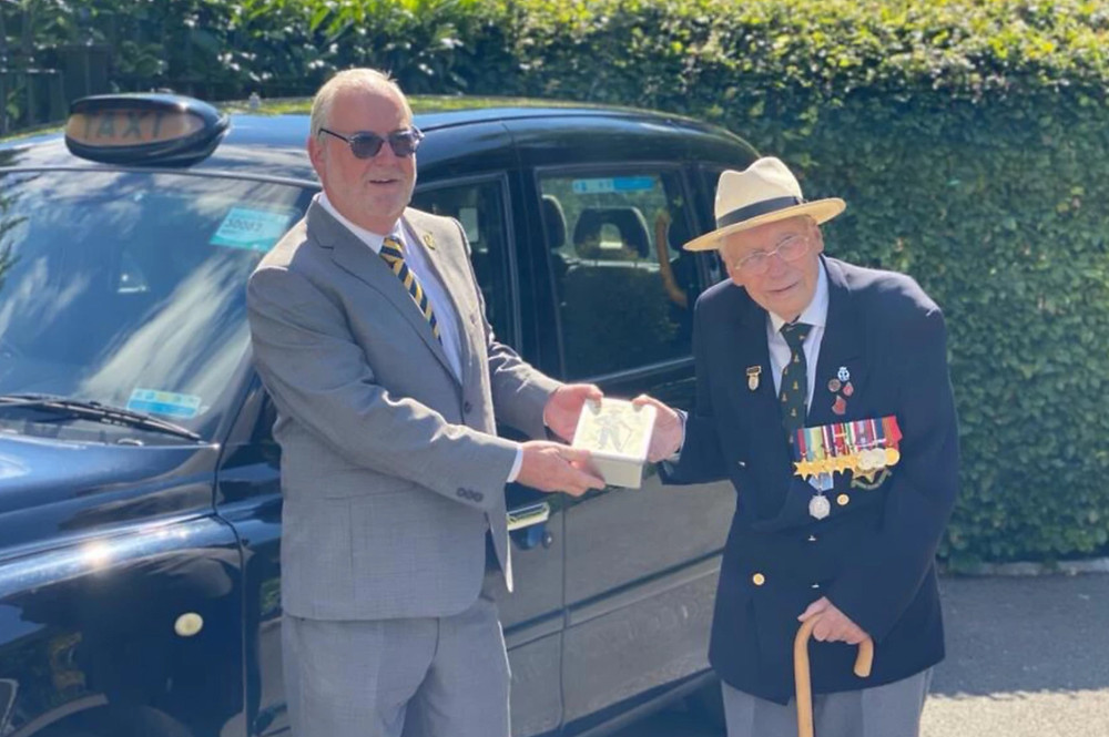 London cabbie and Taxi Charity volunteer Silvi Oliveria delivers a VJ Day commemorative tin to WWII veteran, Roy Miller