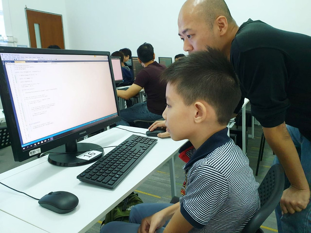 9 year old Yu Yang looking at a computer showing his scripts while the instructor, Siang Leng, looks through the code.