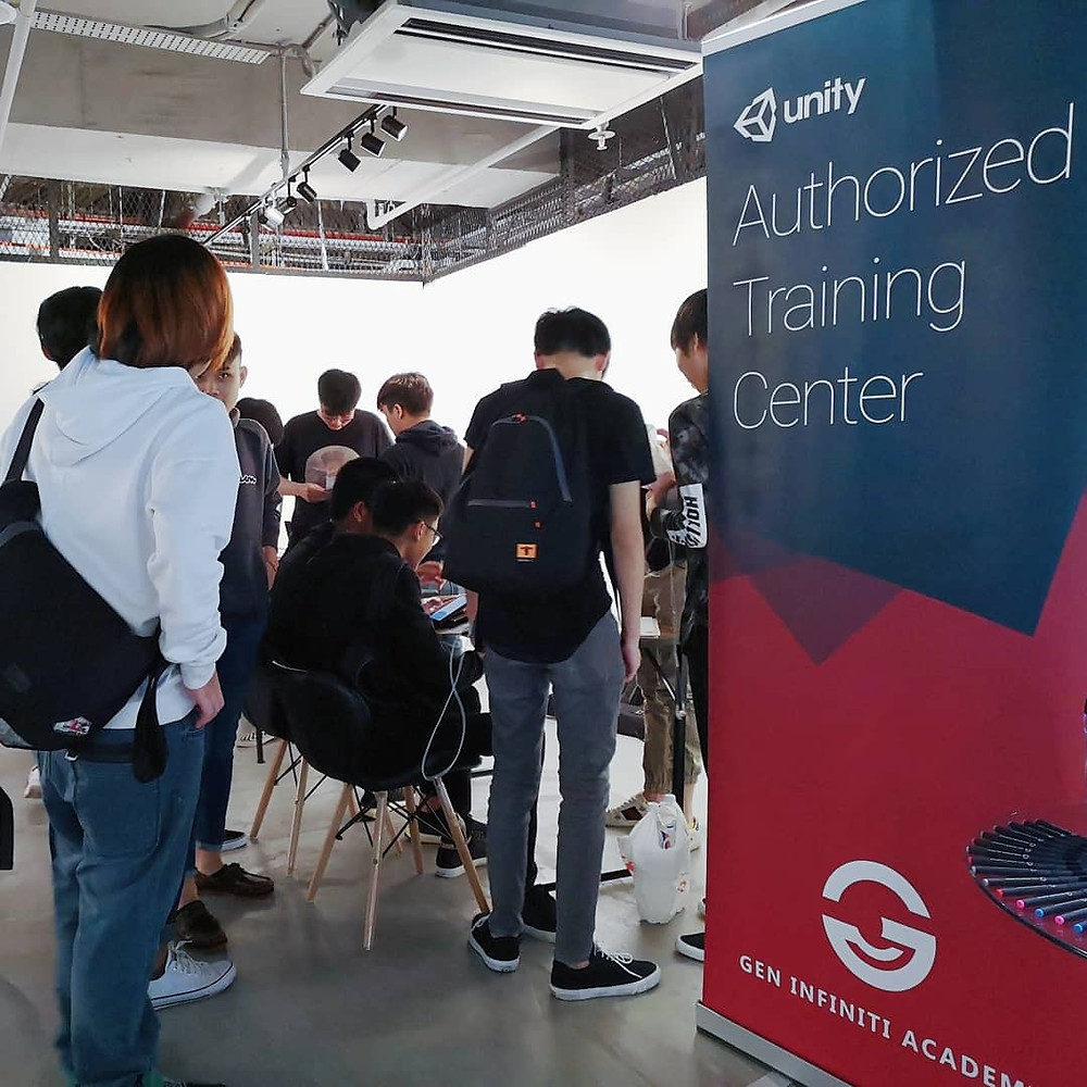 a group of people huddled around a table indicating their interest. next to the table, a banner indicating that Gen Infiniti Academy is a Unity Authorised Training Center
