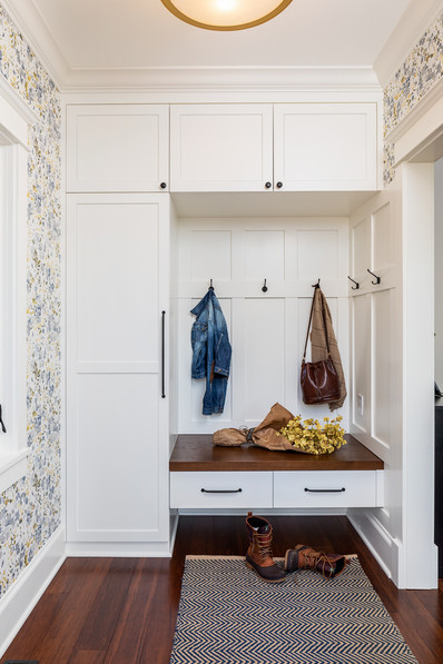 This cheery entry features custom built-in cabinetry with elegant hardware. Mood lifting watercolor patterned wallpaper welcomes you home.