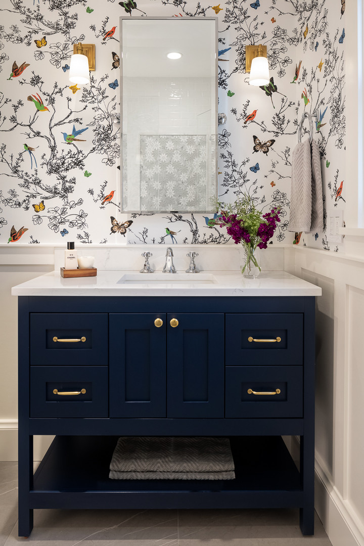 Striking navy vanity paired with Schumacher's Bird & Butterflies wallpaper add a touch of romance to this guest bath.