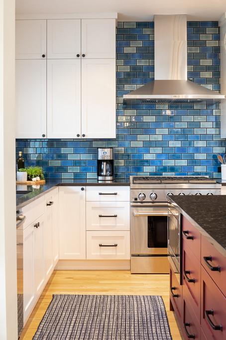 The tile backsplash is made of three shades of blue to create the patchwork pattern.