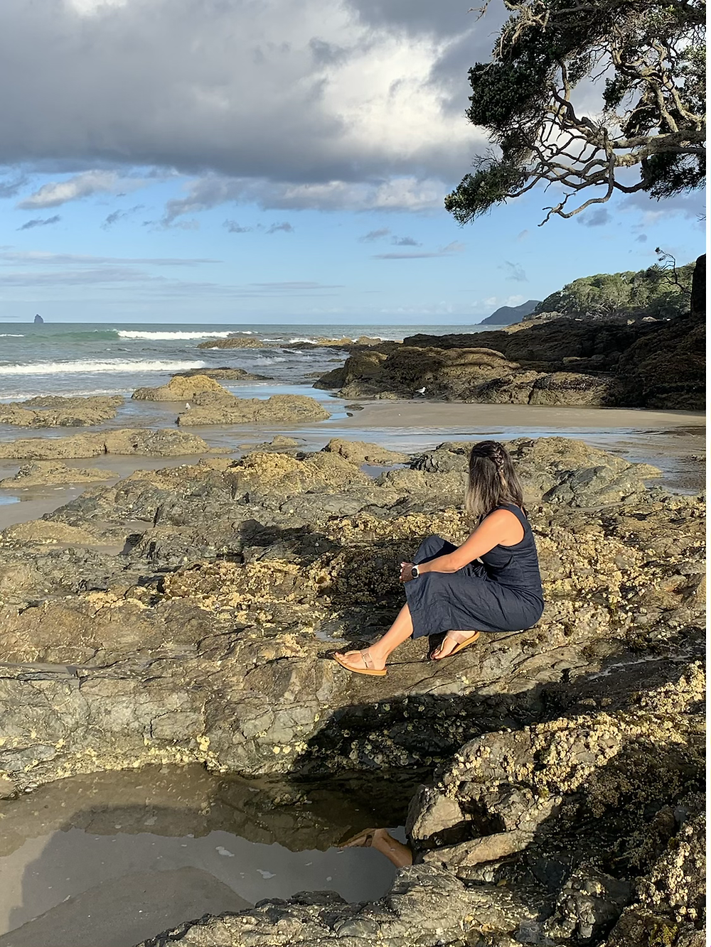 Lady sitting on a rock looking out to the ocean
