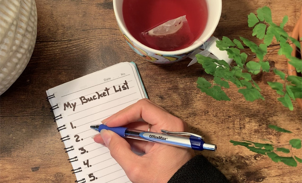 """Cup of tea, a plant and a note pad with the mention of """"Bucket List"""" on it."""