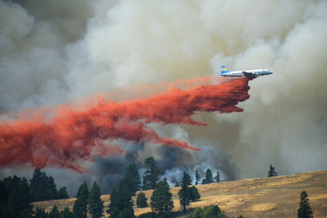 A Douglas DC-7 (a smaller forerunner of the DC-10) drops fire retardant on the Government Flats Complex Fire near The Dalles, Oregon, in 2013.